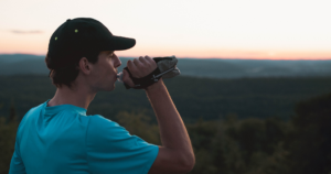 Man drinking from a soft flask while staring at the mountains in front of him